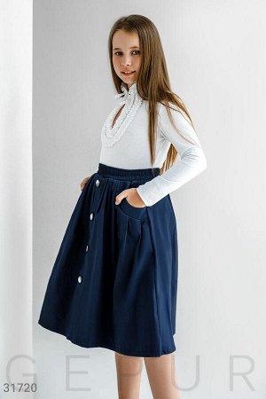 Юбка Расклешенная юбка-полусолнце с высокой посадкой, эластичной вставкой на талии, двумя прорезными карманами по бокам и планкой с декоративными пуговицами спереди.