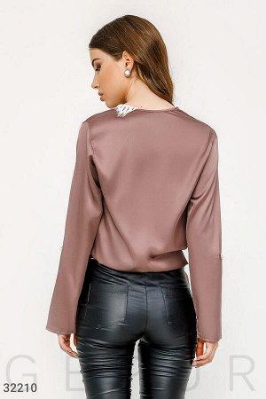 Блуза Классическая шелковая блуза бежевого цвета с перламутровой пуговицей, глубоким v-образным вырезом с кружевом, эластичной вставкой на поясе с завязками.