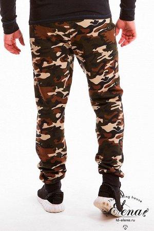 Брюки Спортивные брюки выполнены из футер петли, внизу на манжетах, по бокам размещены вставки из отделочного полотна и карманы. На левом кармане небольшая нашивка. Пояс брюк на резинке. Размерный ряд
