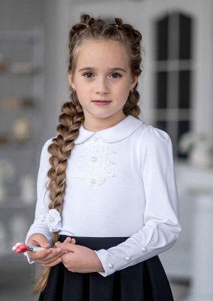 Эмина Модель блузки для младшей возрастной группы. Блузка из трикотажного полотна. Верхняя часть переда, под воротником, оформлена ажурным кружевным декором с пуговицами, создавая имитацию застёжки. Б