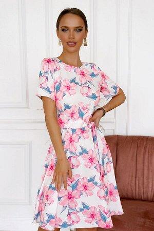 Платье Идеальное летнее платье с цветочным принтом. Цветочные композиции расположены на белом фоне. Такие платья освежают и создают легкий образ. Модель отрезная по линии талии и украшена тканевым рем