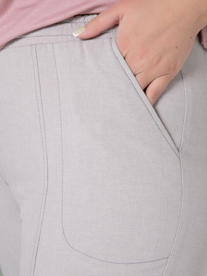 Брюки Брюки-джоггеры полуприлегающего силуэта из ткани с льняной фактурой. Модель на поясе с резинкой и шнуром. - однотонная расцветка - средняя посадка - перед и карманы декорированы отстрочкой контр